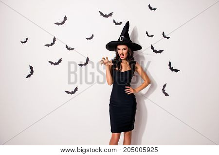Elegant playful mystical female beauty. Gorgeous satanic bad fairy enchantress hot figure slim body fashionable dark dress shows teeth and arm palm with claws stands on white background