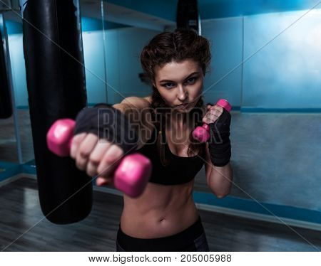 Close up view of young fighter boxer girl with hand bandage punching with pink dumbbells. Woman power and beauty