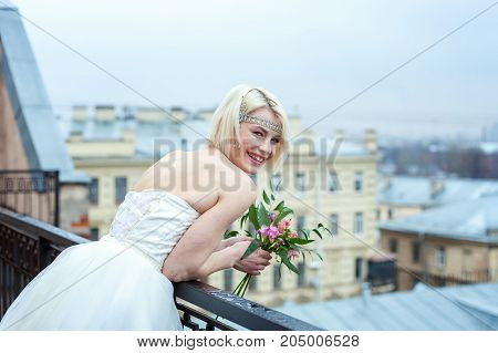 Beautiful young bride on the balcony with perfect landscape