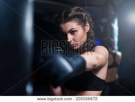 Young fighter boxer fit girl wearing boxing gloves in training with heavy punching bag in gym. Low key image. Woman power. Moment of punch