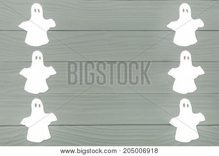 Top view of paper silhouette of six white ghosts made of frame on grey wooden background. Halloween holiday background. Copy space