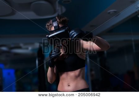 Young fighter boxer fit girl punching in VR glasses wearing boxing gloves in training. Boxing game in virtual reality 360 degrees. Futuristic gaming