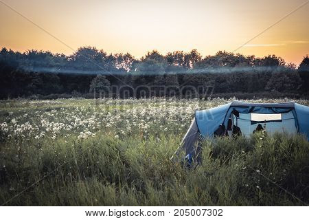 Camping tent on summer rural field with fog and forest on background and orange sunset sky during camping holidays in vintage colors