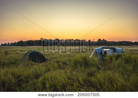Camping tent on summer rural field with forest on background and orange sunset sky during camping holidays