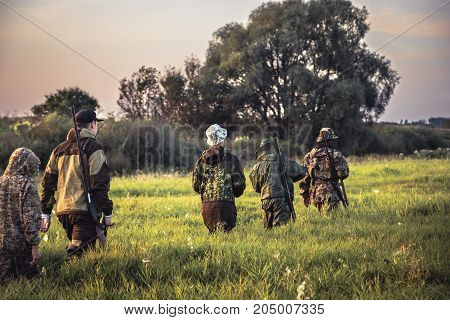 Group of men hunters going through tall grass on rural field at sunset during hunting season