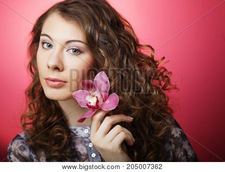 Young curly woman with pink flower over pink background
