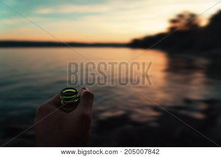 Man holding a beer bottle in hand in front of sunset on shore