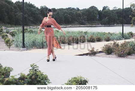 Young fashionable brunette woman wearing long red dress in sunglasses and high heels walks outdoors