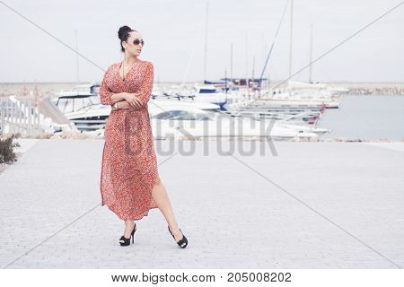 Young fashionable brunette woman wearing long red dress in sunglasses posing near sea, pier with yachts