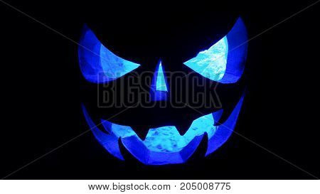 Halloween Concept. An Ominous Pumpkin Isolated In The Dark, With A Blue Cold Glow From The Inside