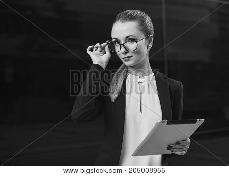 Beautiful blonde woman in suit and glasses with tablet smiling in camera. Business and education concept. black and white copy space