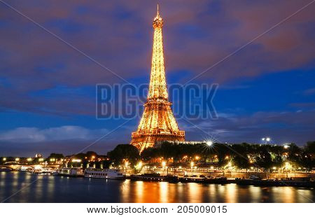 PARIS - 26 APRIL, 2017: Eiffel Tower in the Dusk on April 26, 2017. The Eiffel tower is the most visited monument of France located oh the bank of Seine river in Paris, France.