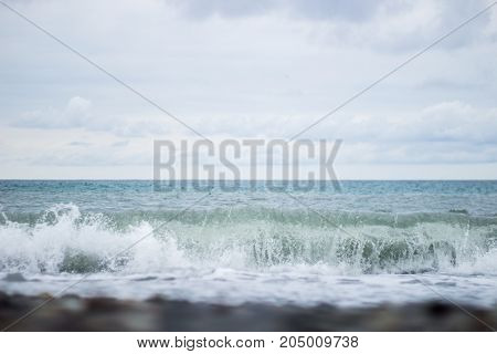 Summer Seascape From The Shore, The Wave Rolls Ashore On The Sea Pebbles