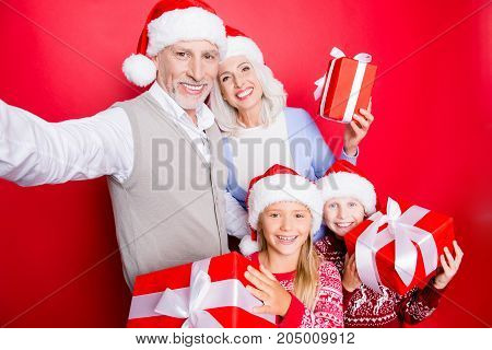 Cheerful Siblings And Married Senior Couple Take And Show Gifts With Ribbons, In Knitted Cute X Mas