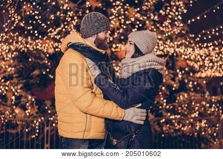 New years eve side profile shot of cheerful happy couple of lovers is cuddling outside look deep into eyes of each other dressed very warm behind them are christmas lights and decorations poster