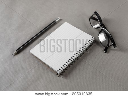 Blank notepad glasses and pencil on craft paper background. Stationery elements. Responsive design mockup.