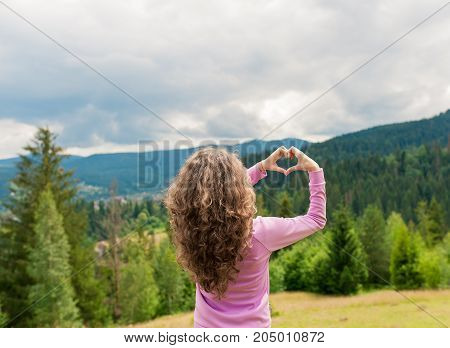 Freedom traveler woman standing with heart shaped hands and enjoy a wonderful nature. Yound girl show hand sign heart on top mountain with perfect view. travel concept