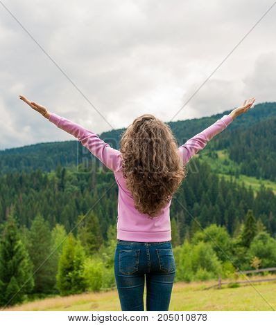 Curly woman happy smiling joyful with arms up dancing on top peak of mountains in summer during holidays. Beautiful young cheerful female model standing back to camera.Young woman outdoors.Freedom concept.