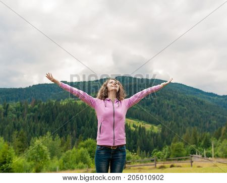 Curly woman happy smiling joyful with arms up dancing on top peak of mountains in summer during holidays. Beautiful young cheerful female model standing to camera. Young woman outdoors.Freedom concept.