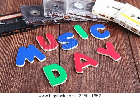 Cassette Tapes With Inscription Music Day On Wooden Table