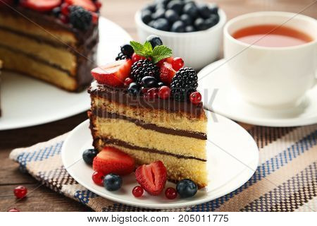 Piece Of Chocolate Cake With Berries In Plate On Wooden Table
