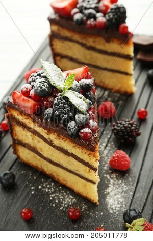 Pieces Of Chocolate Cake With Berries On Cutting Board