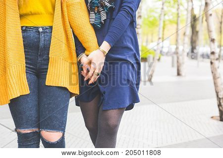 Lesbian Couple Holding Hands And Walking