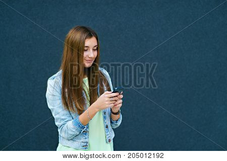 Brunette girl on dark background with phone typing text