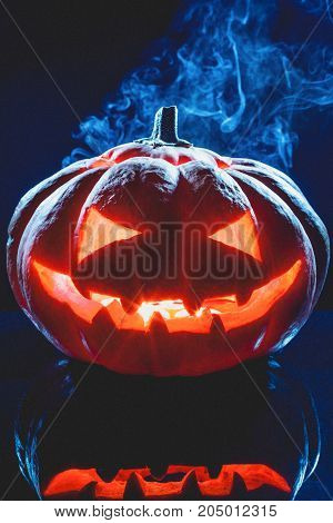 Halloween pumpkin ghost lantern with smoke on dark background