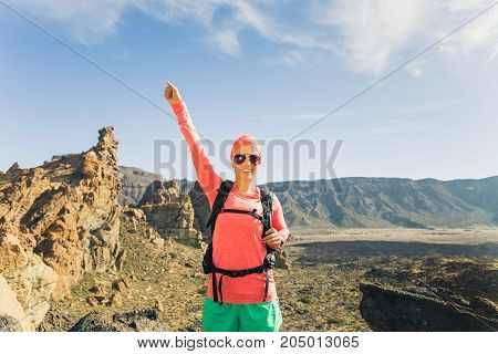 Woman hiker with arms outstretched in mountains. Beauty female runner hands up and enjoy inspirational landscape on rocky trail footpath on Tenerife Canary Islands