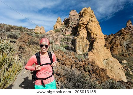 Happy girl hiker walking on mountain trail. Inspire and motivate concept outdoors activity. Female runner or climber looking at inspirational landscape on rocky trail on Tenerife Canary Islands