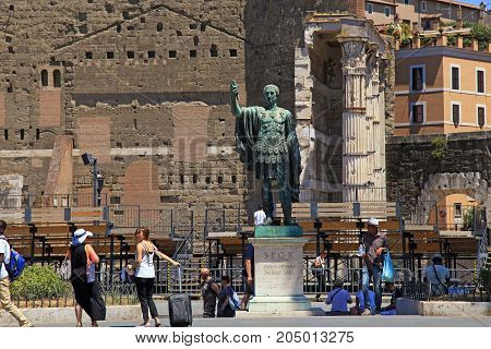 ROME, ITALY - JULY 17, 2017: Tourists and bronze statue of emperor Julius Caesar on Via dei Fori Imperiali near Roman Forum, Rome, Italy.