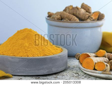 Composition of turmeric used a spice in cooking and heath benefits clay bowl with light blue background selective focus to add copy space
