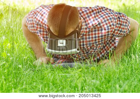 Man In A Helmet Of Virtual Reality Lies On A Green Grass And Looking Down
