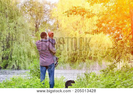 Dad With A Little Son Are Standing On The Shore Of A Forest Lake, Rear View