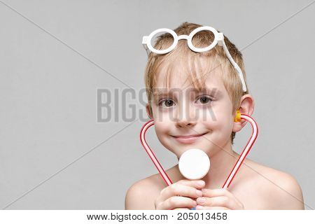 Cute Boy Is Playing Doctor. Toy Glasses And Phonendoscope. Portrait