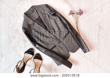 Gray Jacket With A Leather Sleeve, Black Shoes, Wild Flowers. Fashionable Concept On White Fur