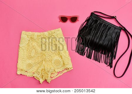 Yellow Lace Shorts, Black Bag With Fringe And Rose-colored Glasses. Bright Pink Background