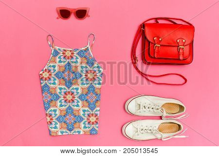 Top In Ornament, Red Handbag, White Sneakers And Rose-colored Glasses. Bright Pink Background, Close