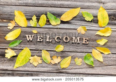 Phrase Welcome On A Wooden Background, Frame Of Yellow Leaves