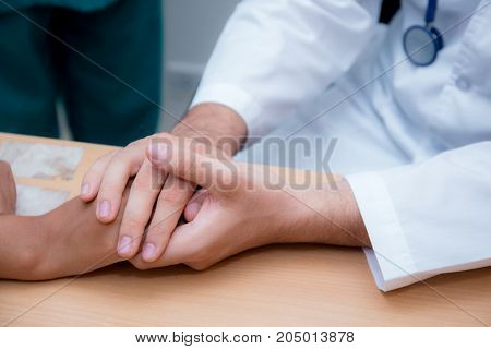 Friendly Male Doctor Hand Holding Patient Hand Sitting At The Desk For Encouragement - Empathy - Che