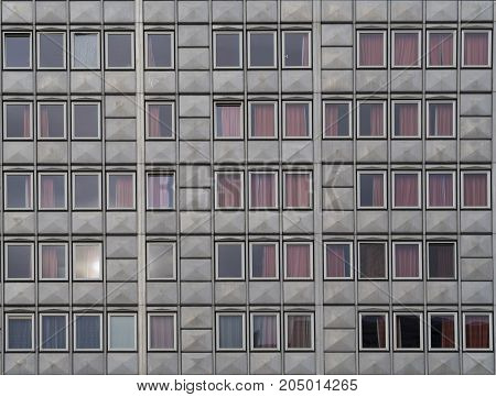 detail of prefabricated panel house wall of windows with red curtains urban background