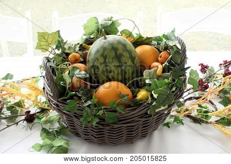 Basket of artificial fruits and vegetables on a white tablecloth in an outdoor setting.