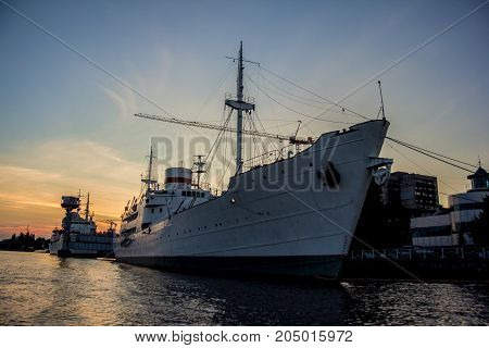 Evening port in Kaliningrad Cargo ship in the harbor on sunset background