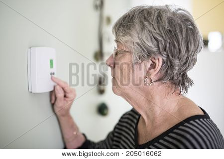 A Senior woman adjusting her thermostat at home