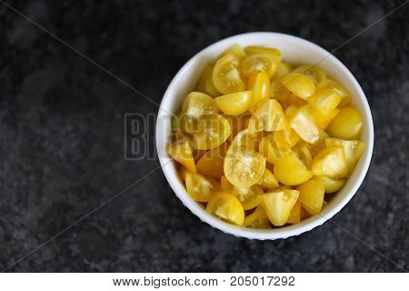 Bowl of chopped heirloom yellow pear tomatoes. Room for text.