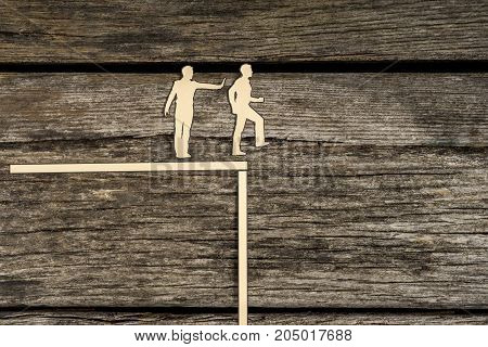 Small silhouette cutout men standing next to each other as one pushes another off the edge of a cliff over wood background.