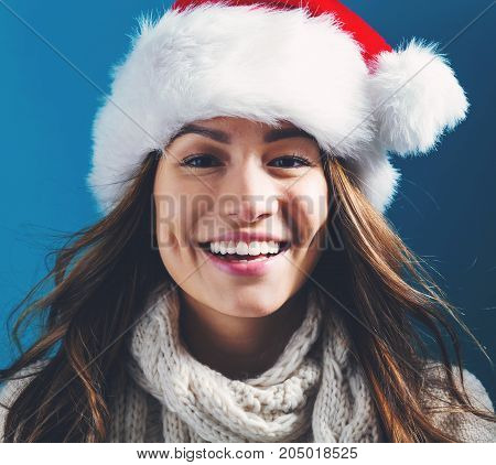 Happy young woman with Santa hat on a dark blue background