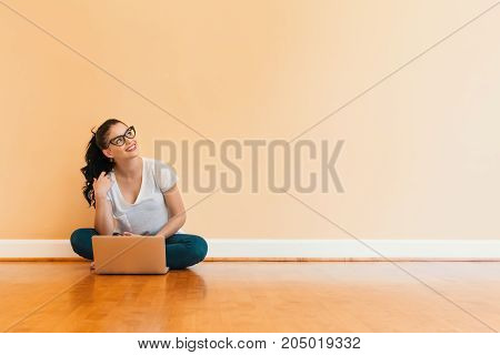 Young woman using her laptop in a big room
