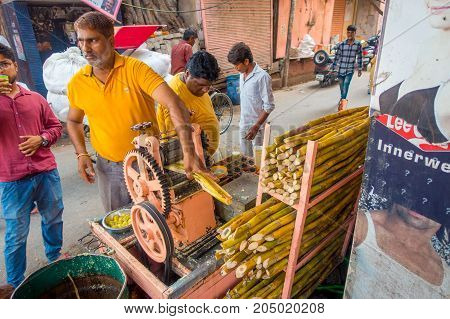 Jaipur, India - September 20, 2017: Unidentified man working with a machine to extract refreshing juice from sugar cane, in an alley in Jaipur, India.
